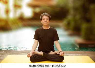 Excersice yoga everyday is good for your health. It make you look very young, fit and firm. A sage posture, siddhasana, sitting close eyes relaxing posture beside outdoor pool.