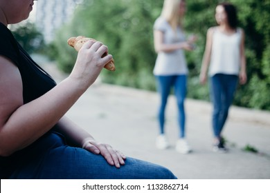 Excess weight, overeating, obesity, bad habits and lifestyle. Overweight woman envy to fit girls sitting in the street eating fattening snack
