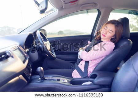 Excessively tired young Asian women driving,sleeping in car