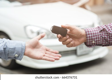 exchange handing over the car keys for to a young businessman.