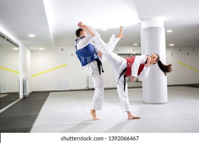 Exchange of high kicks during training of taekwondo between two fighters