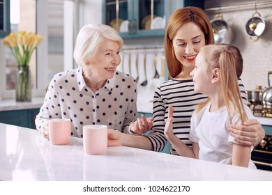 Exchanging thoughts. Pleasant little girl sitting at the kitchen counter next to her mother and grandmother and chatting with them serenely