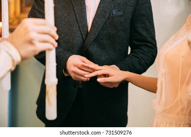 exchanging wedding rings. priest putting on golden wedding rings on fingers bride and groom in church at wedding matrimony. traditional religious wedding ceremony