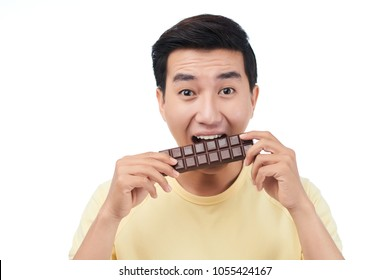 Excite young Vietnamese man eating chocolate bar