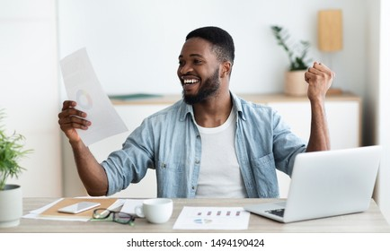 Excited african american businessman checking financial reports and celebrating success of his company, panorama