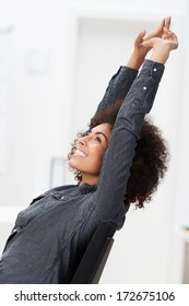 Excited African American businesswoman smiling in jubilation and raising her arms in the air as she relaxes in her chair at the office