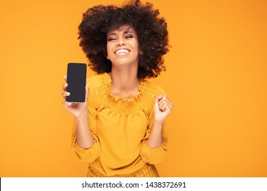 Excited african american girl hold mobile phone with blank empty screen isolated on yellow studio background . Emotions, lifestyle concept. Copy space.