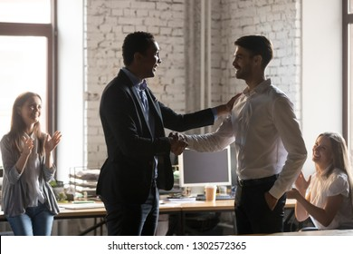 Excited African American male employer handshake and tap shoulder of male worker congratulating with success, smiling black businessman or boss shake hand of employee greeting with promotion