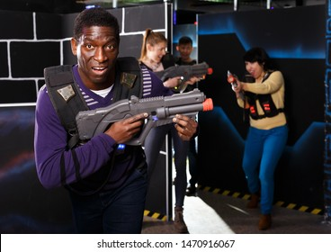 Excited African American man aiming laser pistol at other players during lasertag game in dark room