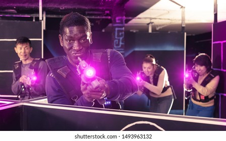 Excited African American man aiming laser gun at other players during lasertag game in dark labyrinth