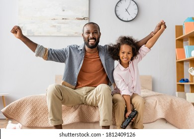 excited african american man with daughter showing winner gesture while looking at camera