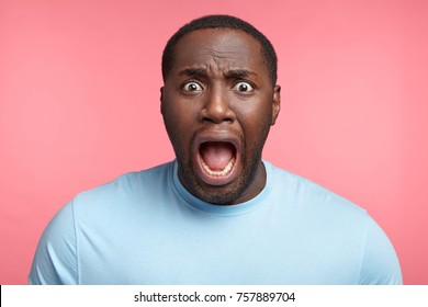 Excited African American man screams in panic, gaze with bugged eyes, shocked to hear bad news. Surprised male has stressful situation. Great astonishment, disbelief, facial expressions concept