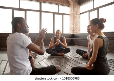 Excited african american man talking to sporty happy diverse friends sitting on mat in studio, happy black yoga instructor or life coach motivating young people having fun at seminar training class