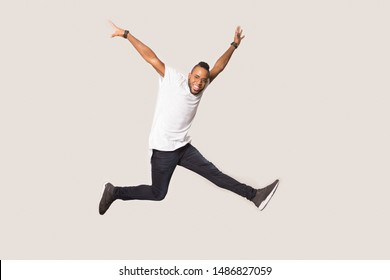 Excited african American millennial man in glasses and casual wear have fun in studio, smiling black male in eyewear jump high raise hands up in air feel happy euphoric, entertain during photoshoot