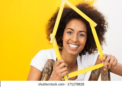 Excited African American woman in her new home holding up a wooden frame in the shape of a house to celebrate her achievement as she stands in front of a half painted wall