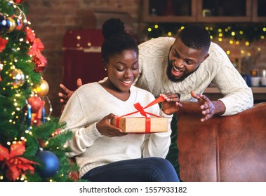 Excited african american woman opening Christmas gift from her boyfriend at home, sitting on sofa near Xmas tree