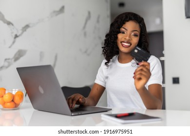 Excited African American woman ordering food online. Beautiful woman with emotional face using credit card and laptop for online shopping, making transaction, standing on white kitchen at home
