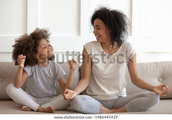 Excited african american woman teaching cute little adorable daughter meditating and practicing yoga exercises. Happy mixed race family sitting on comfy couch in lotus position, having fun together.