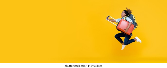 Excited African American woman tourist woman with backpack and luggage jumping in mid-air  isolated on colorful yellow banner background with copy space