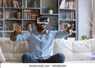 Excited African American young man in virtual reality glasses touch objects interact with 3D simulation, happy biracial male in VR goggles have fun testing new device, digital technology concept
