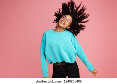 Excited african american young woman with bright smile dressed in casual clothes, glasses and headphones dance over pink background.