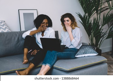 Excited african american young woman and caucasian hipster girl shocked with last fashion news on website.Wondered diverse friends watching strange video on laptop computer using home internet