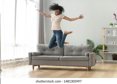 Excited african American young woman have fun in living room jump high up in air, happy black biracial millennial girl feel overjoyed motivated, enjoy good weekend at home, moving relocation concept