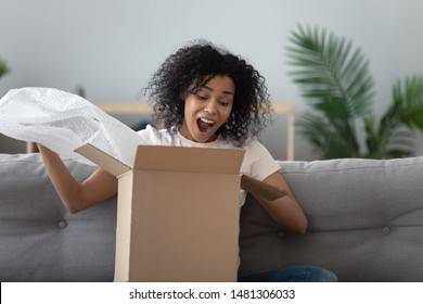 Excited african American young woman sit on couch at home unpack cardboard box shopping online, overjoyed black millennial girl buyer feel euphoric open shipped package parcel from delivery service