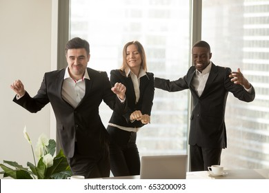 Excited african and caucasian employees dancing in office, staff party, positive multi-ethnic team satisfied with result, won profitable contract, group of winners celebrate victory or great success