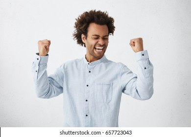 Excited African male winner raising his fists with great happiness having good mood after winning game. Young champion having success being glad to achieve his goals. Victory and triumph concept