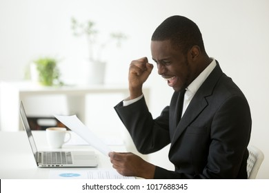 Excited african-american businessman holding letter with unexpected good news, happy black entrepreneur celebrating unbelievable win success achievement reading notification notice, got job promotion