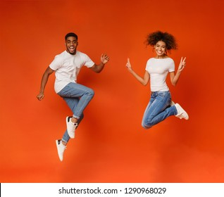 Excited african-american couple jumping, having fun on orange background