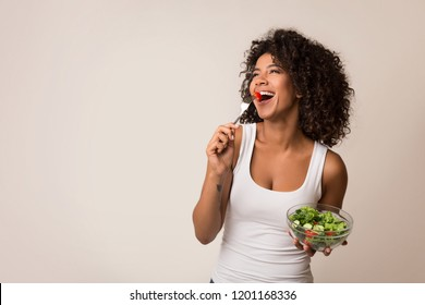 Excited african-american lady eating healthy salad over light background