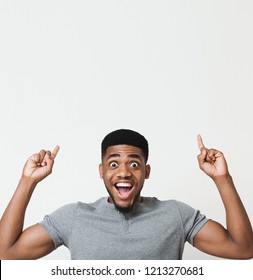 Excited african-american man having an idea and pointing two fingers up at copy space, white studio background