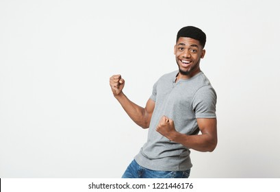 Excited african-american man shaking clenched fists, celebrating his victory or triumph, rejoicing successful deal, copy space