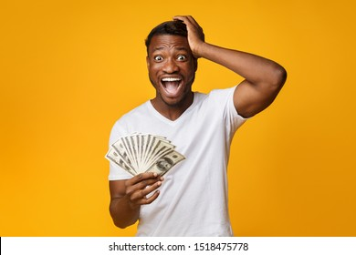 Excited Afro Guy Holding Money Shouting Touching Head Standing On Yellow Studio Background. Big Luck. Free Space