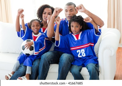 Excited Afro-American family watching a football match at home
