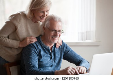 Excited aged husband using laptop showing smiling wife something on screen, happy senior couple looking at computer, watching pictures together or funny video online. Elderly and technology concept