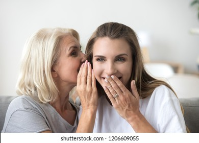Excited aged mother whisper in daughter ear sharing secret with her spending time together at home, happy young woman laugh and giggle having fun with elderly mom, sincerely talking or gossiping
