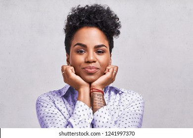 Excited amazed beautiful African American female looks with joyful expression, keeps hands under chin, expresses great satisfaction, being pleased to receive gift, isolated over blank background.