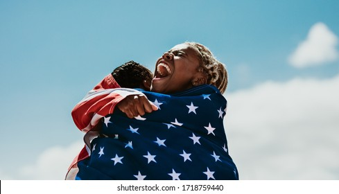 Excited american female athletes wrapped in national flag hugging each other after a winning the race. Team of USA female runners rejoicing a victory outdoors.