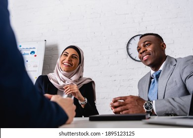 excited arabian businesswoman laughing during meeting with african american business partner and interpreter, blurred foreground