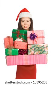 Excited Asian girl Santa Claus hat with pile of Christmas gifts wrapped in colorful paper and decorated by bows