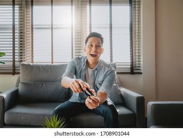 Aufgeregt asiatischer Mann, der im Wohnzimmer zu Hause Videospiel spielt und Fernsehbildschirm und Regler anschaut