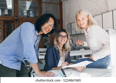 Excited asian student in blue shirt preparing for exams with caucasian female girl in glasses. Smiling chinese boy explains task to european university friends.