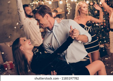 Excited attractive charming beautiful cheerful well-dressed couple, husband holds, bends elegant wife, latin dance, ladies and handsome gentlemen at home festive, chill out, glitter falling down