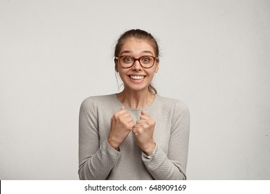 Excited attractive female student wearing stylish glasses clenching fists and raising eyebrows, having impatient look, waiting for results of college competition, anticipating her success and victory