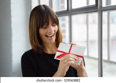 Excited attractive middle-aged woman opening a festive envelope tied with a red ribbon as she stands indoors in front of a window
