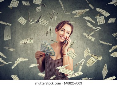 Excited attractive woman talking on a smartphone holding money, cashback under dollar rain