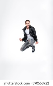 Excited attractive young man screaming and jumping over white background